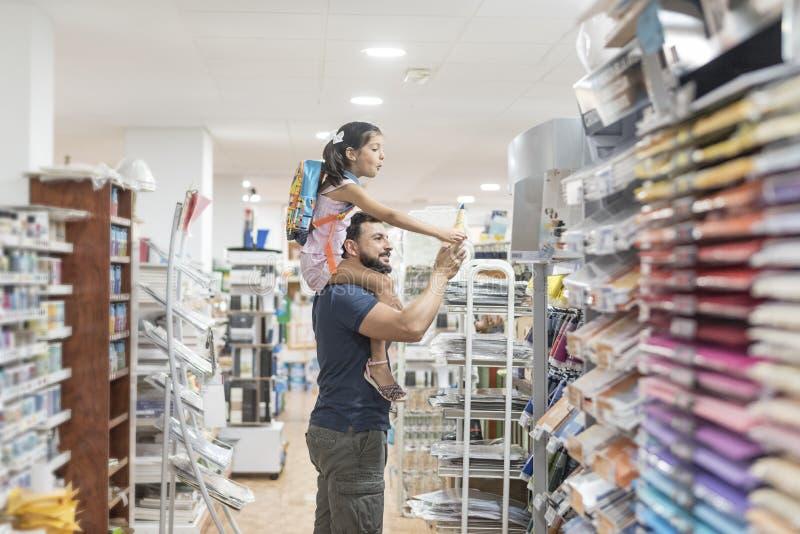 Fuentes de escuela de compra del padre y de la hija que se preparan para volver a la escuela, preparándose para septiembre imagen de archivo libre de regalías