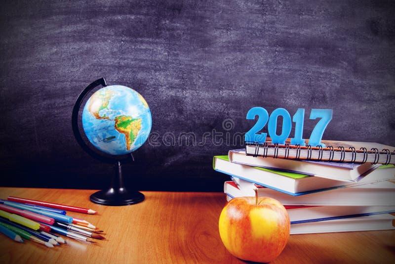 Fuentes de escuela con los números 2017 en una pila de libros y una manzana en fondo de la pizarra con el copyspace para su texto fotografía de archivo