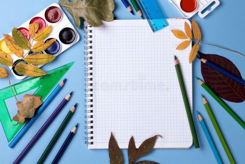 Fuentes de escuela en fondo azul con las hojas de otoño imagen de archivo libre de regalías
