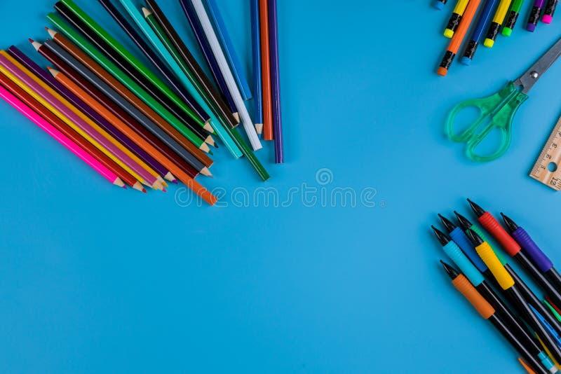 Fuentes de escuela, frontera superior coloreada de los lápices en un fondo azul imagen de archivo