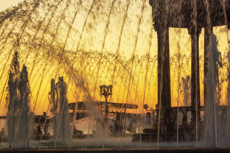 Fuentes de la ciudad en la 'promenade' del mar en la puesta del sol imagenes de archivo