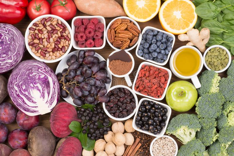 Fuentes de la comida de antioxidantes naturales tales como frutas, verduras, nueces y polvo de cacao fotos de archivo