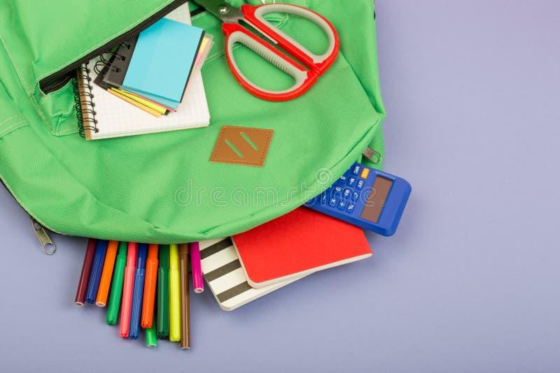 Fuentes de la mochila y de escuela: cuaderno de notas, rotuladores, tijeras, calculadora en fondo del papel azul fotos de archivo