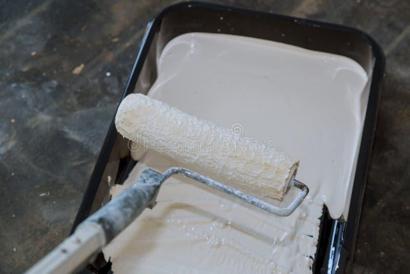 Fuentes de la pintura de casa, herramientas del pintor en una bandeja con el rodillo de pintura fotografía de archivo