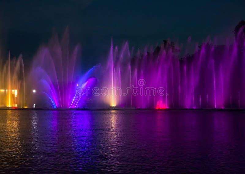Fuentes del canto Fuentes coloreadas que brillan intensamente y demostración del laser imagenes de archivo
