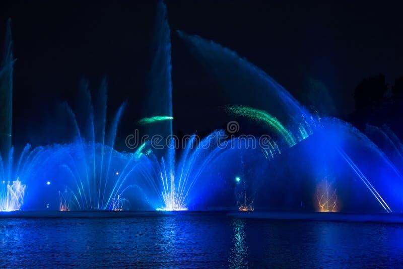 Fuentes del canto Fuentes coloreadas que brillan intensamente y demostración del laser fotos de archivo