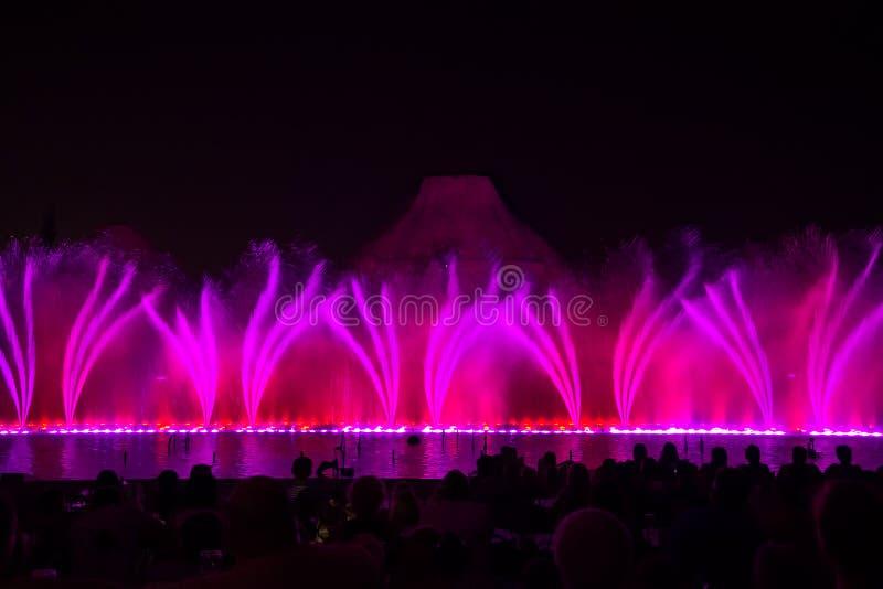 Fuentes del canto Fuentes coloreadas que brillan intensamente y demostración del laser imagen de archivo