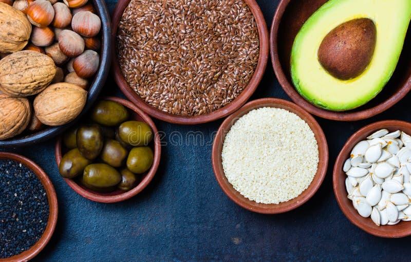 Fuentes gordas sanas vegetarianas Nueces, aguacate, aceitunas, semillas foto de archivo