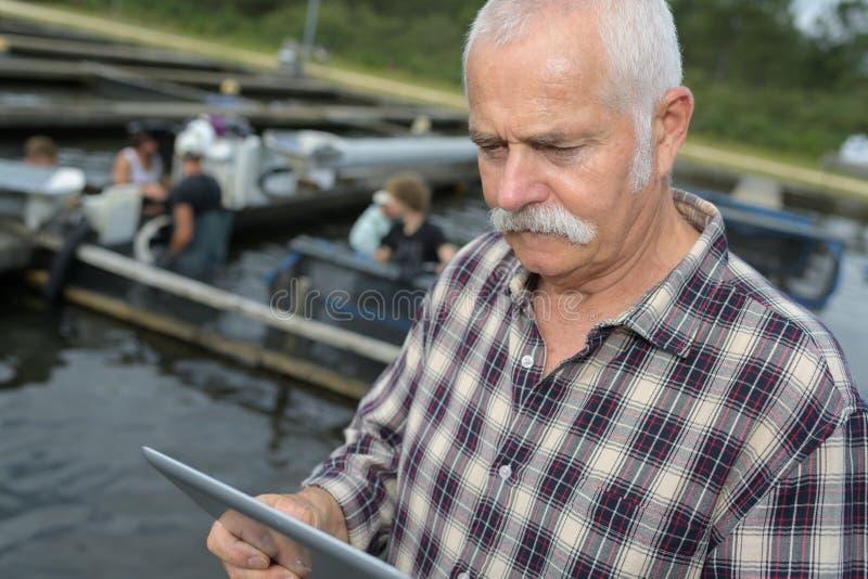 Fuentes que ordenan del encargado de la granja de los crustáceos o de pescados en la tableta imágenes de archivo libres de regalías
