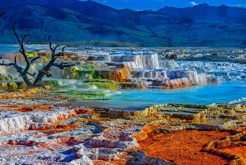 Fuentes termales con colores múltiples y montañas azules en el fondo foto de archivo