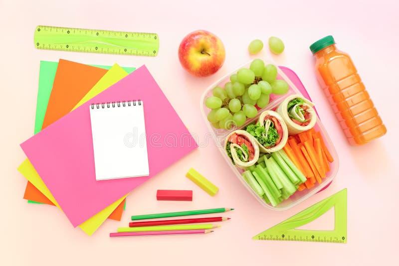 Fuentes y fiambrera de escuela con los rollos sabrosos, pepinos, zanahorias, uvas, manzana, botella de jugo en rosa claro imagen de archivo libre de regalías
