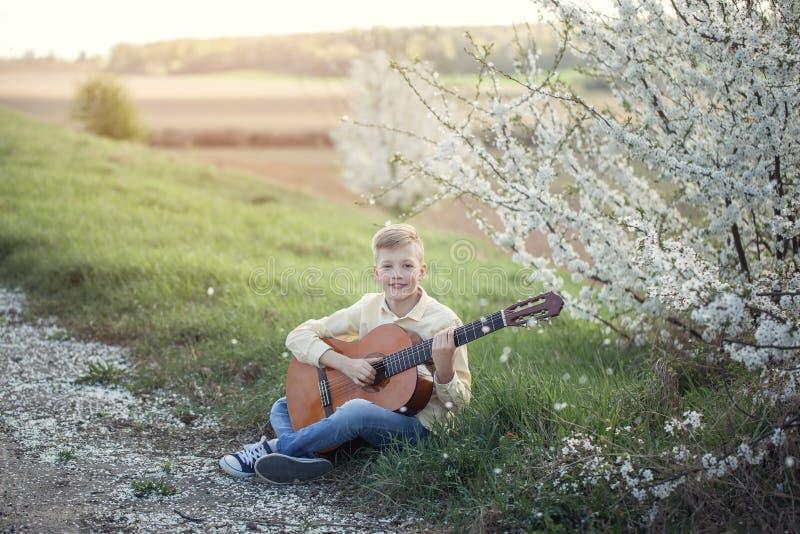Fuera del retrato de un adolescente joven que toca la guitarra en parque de la primavera fotografía de archivo