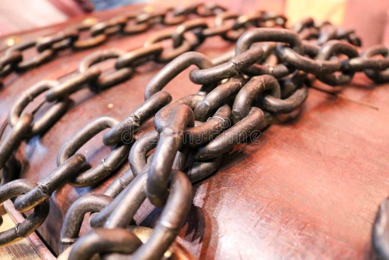 Fuerte, hierro, cadenas viejas en un fondo de madera imagenes de archivo
