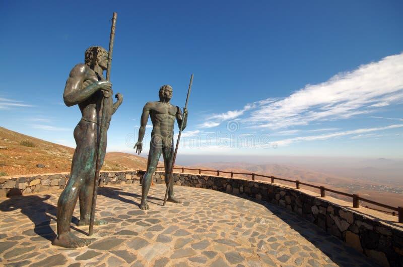 Fuerteventura - bronsstatyer av två konungar Ayose och klädsel på t arkivbilder