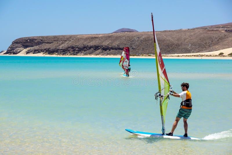 Fuerteventura, Canarische Eilanden 08 Juni 2017: Een mens geniet van het windsurfing het is noodzakelijk om het gebruiken van een royalty-vrije stock afbeelding