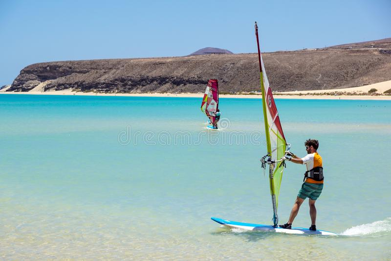 Fuerteventura, wyspa kanaryjska 08 2017 Czerwiec: Mężczyzna cieszy się windsurfing ja jest konieczny uczyć się używać kipieli szk obraz royalty free