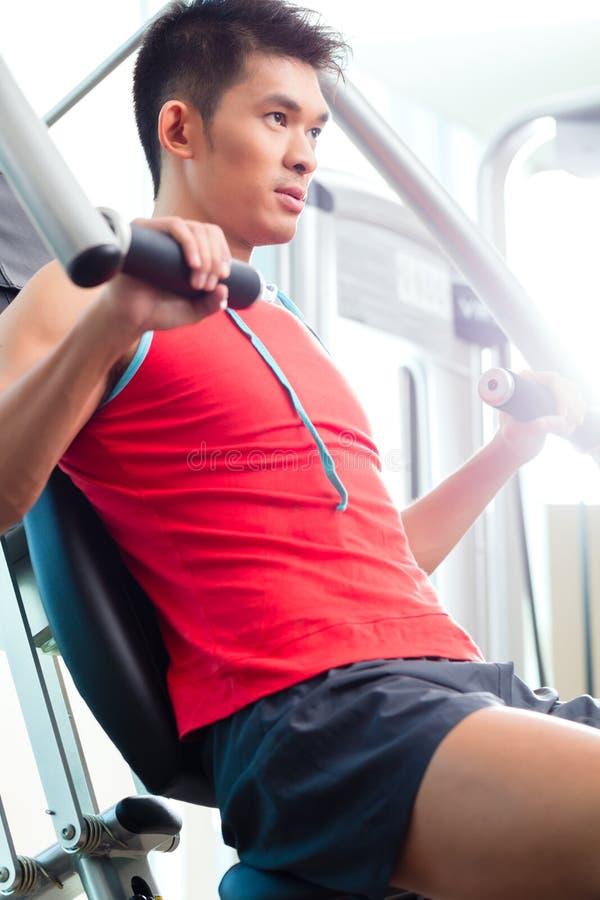 Fuerza china del entrenamiento del hombre en gimnasio de la aptitud imagenes de archivo