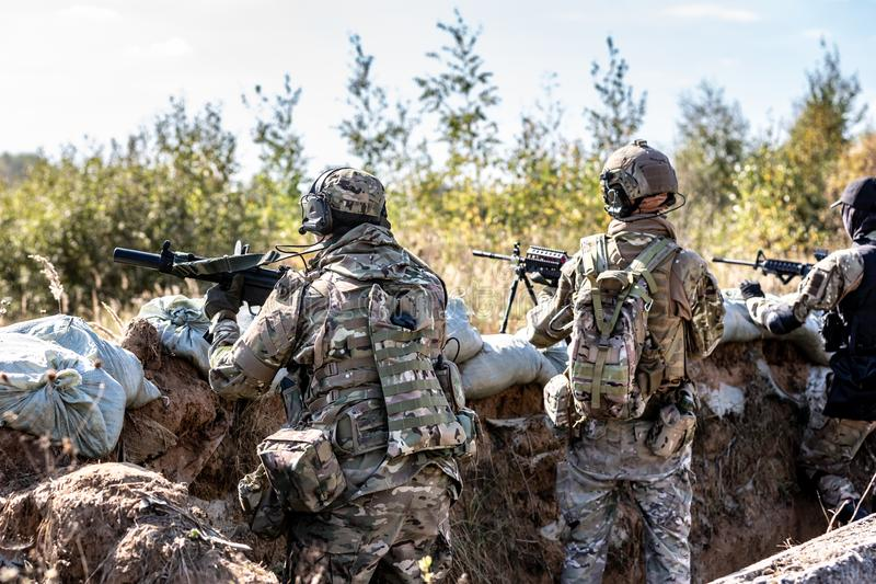 Fuerzas especiales, rifle de asalto del soldado con el silenciador, vista óptica detrás de la cubierta que espera en emboscada fotografía de archivo libre de regalías