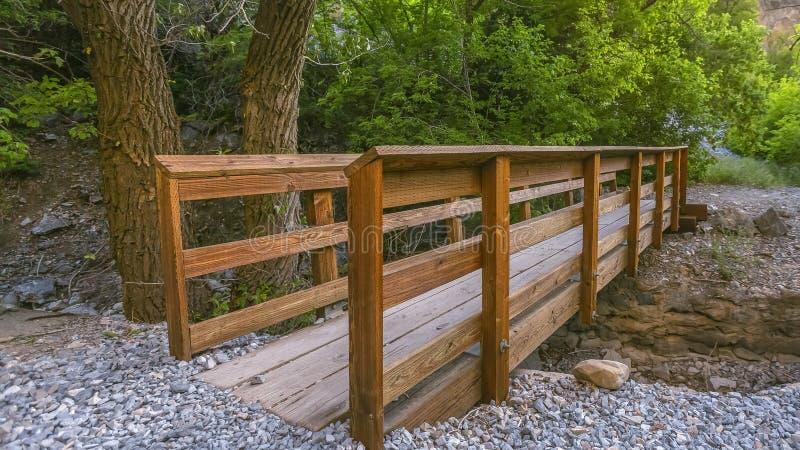 Fuga de caminhada com ponte de madeira sobre um córrego rochoso fotos de stock