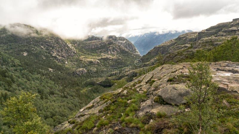 Fuga de caminhada no preikestolen, no fiorde Lysefjor da distância imagem de stock royalty free