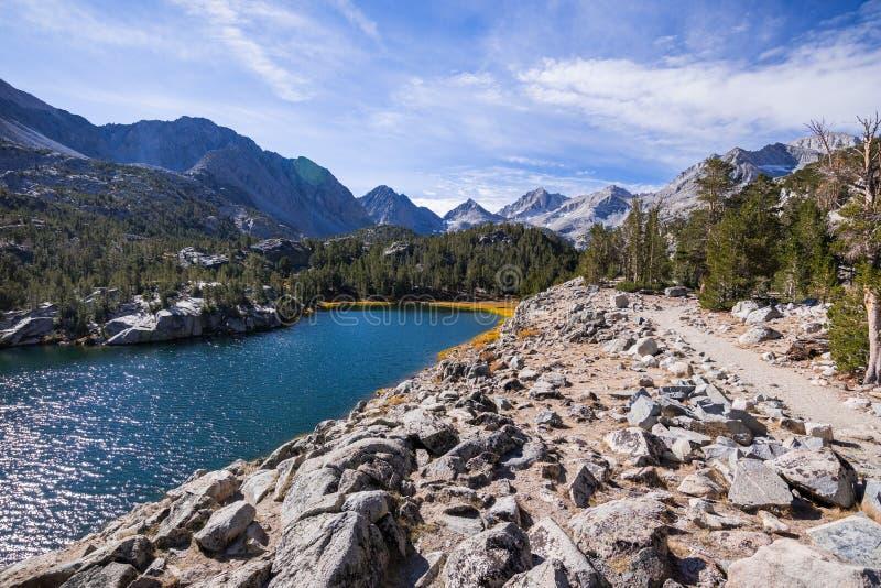 Fuga de caminhada que segue a linha costeira de um lago alpino fotografia de stock royalty free