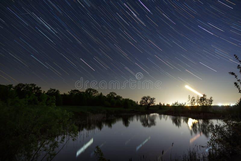 A fuga de protagoniza no céu noturno em torno da estrela norte sobre o lago fotografado com uma exposição longa no fundo foto de stock royalty free