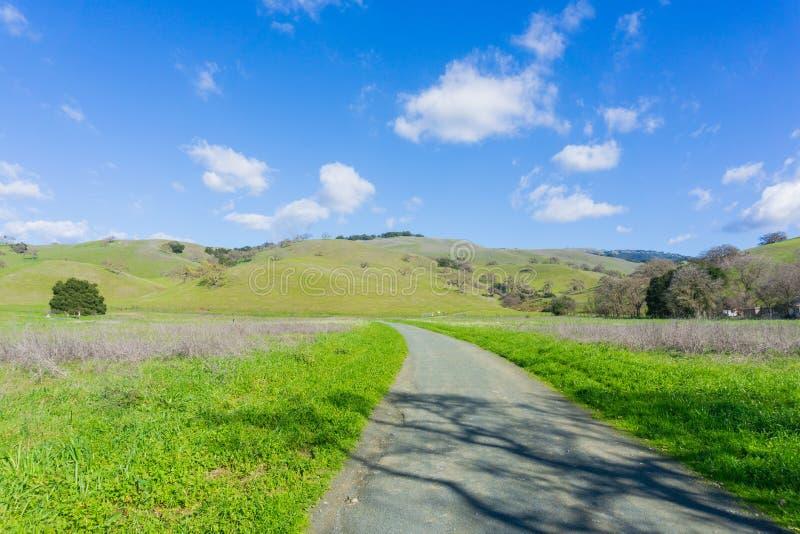 Fuga do cascalho que conduz aos montes verdes e aos vales no lago coyote - Harvey Bear Park, Morgan Hill, Califórnia foto de stock