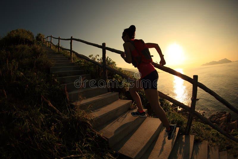 Fuga do corredor da mulher da aptidão que corre em escadas da montanha do beira-mar imagens de stock royalty free