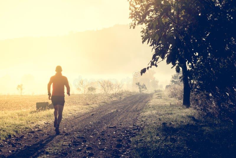 Fuga do homem que corre no país fotografia de stock royalty free