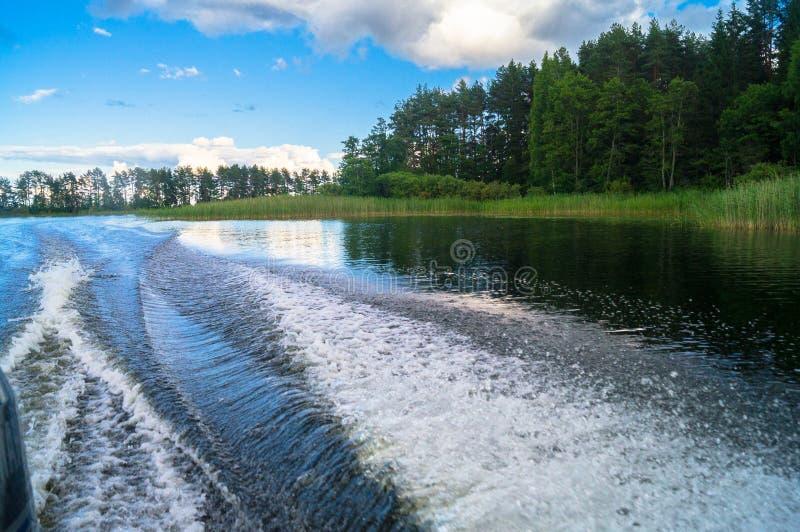 Fuga espumosa na superfície da água atrás do barco a motor movente rápido O lago Seliger, Rússia fotos de stock royalty free