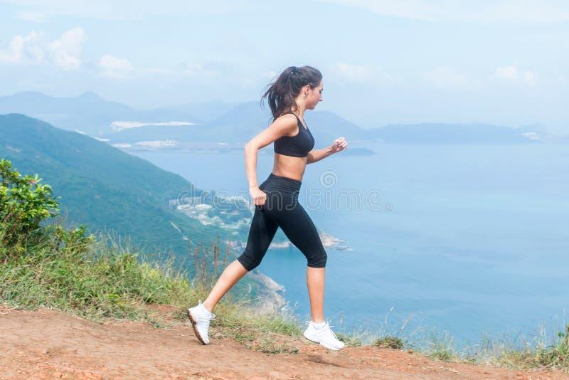 Fuga fêmea através dos campos do corredor que corre no trajeto da montanha no verão Mulher que veste o sportswear preto que exerc fotografia de stock