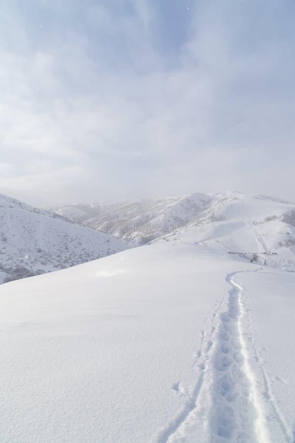 Fuga na neve nas montanhas imagem de stock