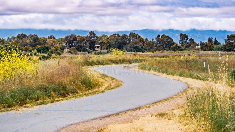Fuga pavimentada que segue a linha costeira de área de San Francisco Bay sul, Mountain View, Califórnia imagens de stock royalty free