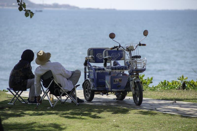 Fuga romântica, par que relaxa pela praia com velomotor elétrico, dia imagens de stock royalty free