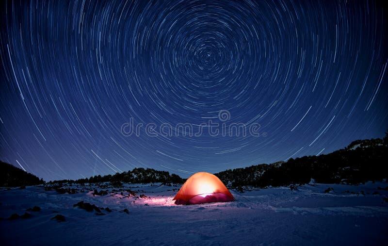 Fugas da estrela na barraca iluminada na neve imagens de stock