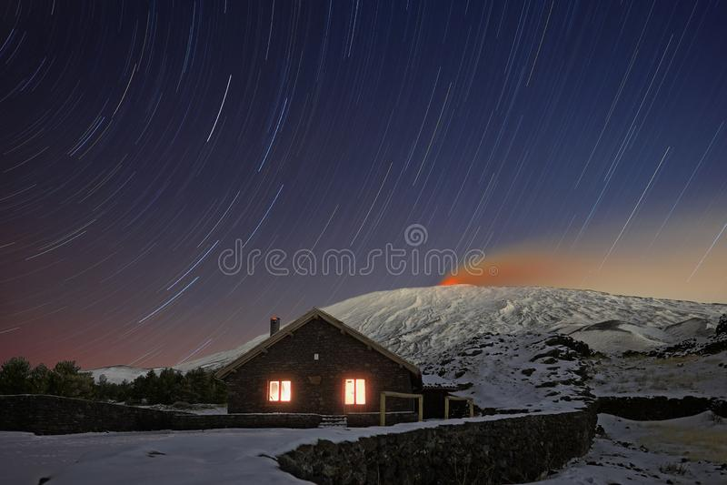 Fugas da estrela no refúgio de Galvarina com as janelas que incandescem sob Etna Volcano nevado foto de stock