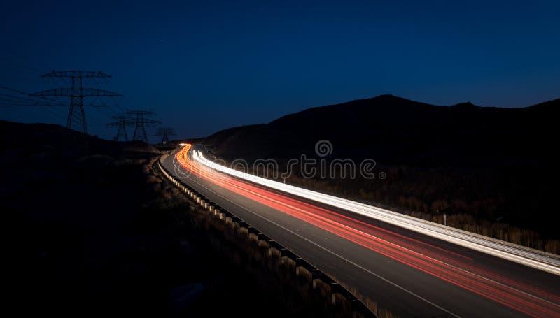 Fugas da luz dos carros moventes rápidos imagem de stock