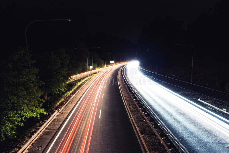 Fugas do carro em uma estrada da noite foto de stock royalty free