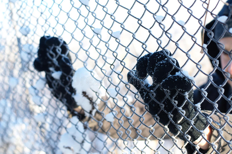 Fugitive behind the grid. Man in gloves behind the freezed grid stock images