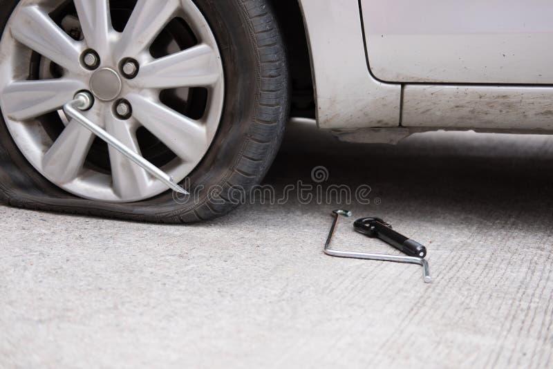 Fuite de pneu de voiture en raison du broyage de clou pneu plat sur la route flatt photographie stock libre de droits