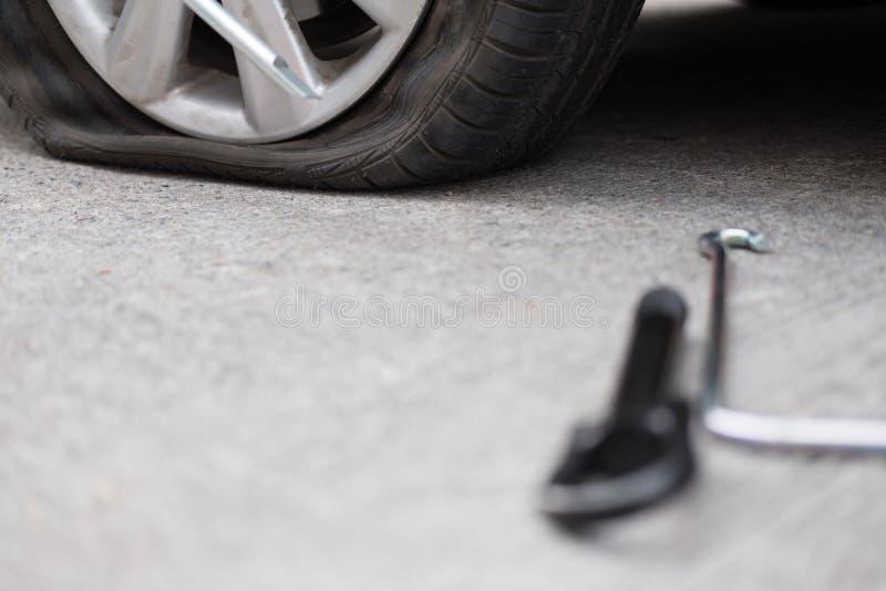 Fuite de pneu de voiture en raison du broyage de clou pneu plat sur la route flatt photos libres de droits