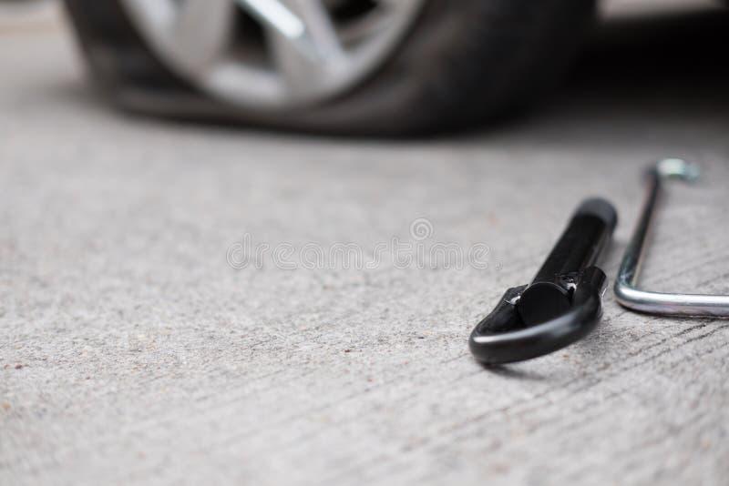 Fuite de pneu de voiture en raison du broyage de clou pneu plat sur la route flatt images libres de droits