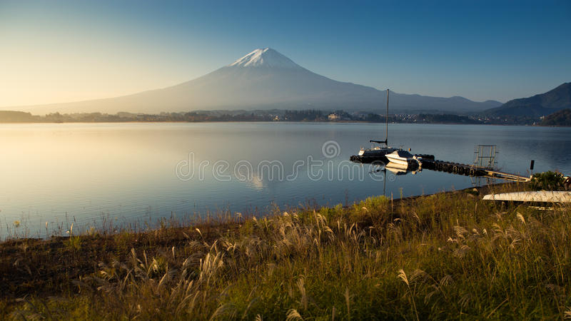 Fuji mountain at sunrise from Kawaguchiko lake. In autumn season. maple color changing from yellow to red royalty free stock images