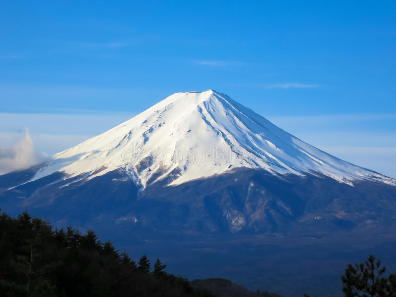 Fuji mountain top filled with white snow and blue sky background royalty free stock photography