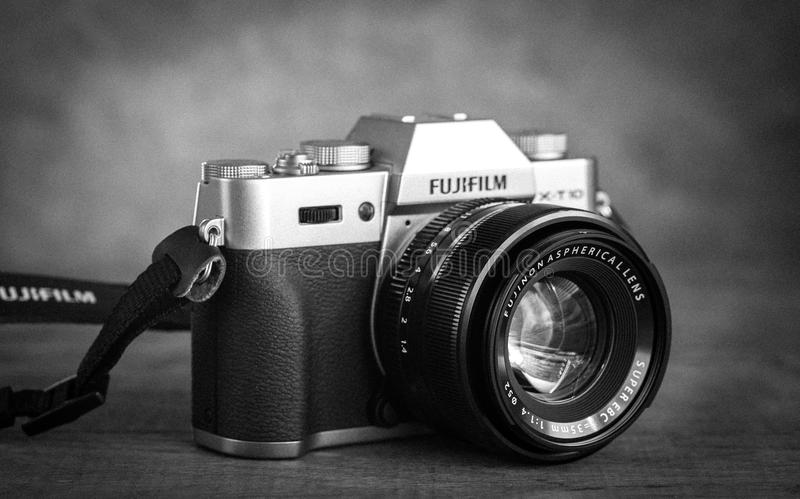 Fujifilm X-T10 Mirrorless Digital Camera. SUMY, UKRAINE - SEPTEMBER 7, 2016: Fujifilm X-T10 Mirrorless Digital Camera on vintage background. Old fashioned black royalty free stock images