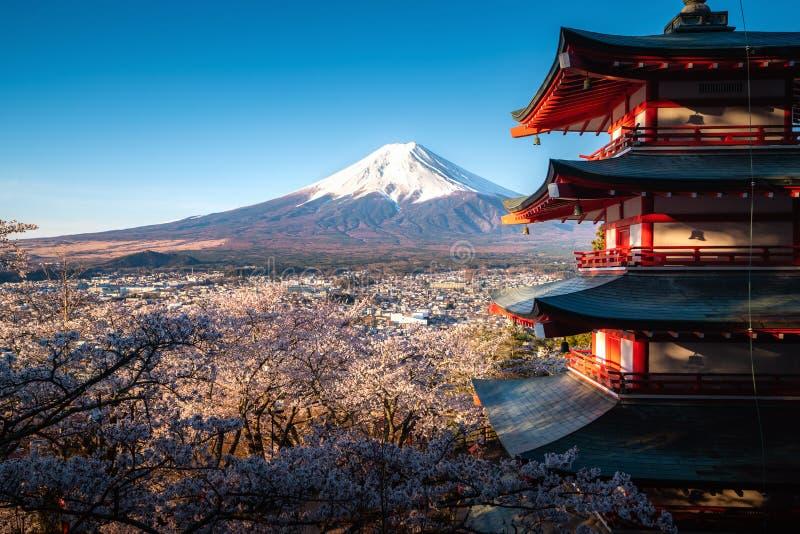 Fujiyoshida, Japan p? den Chureito pagoden och Mt Fuji på våren med full blom för körsbärsröda blomningar under soluppgång Lopp o arkivfoton