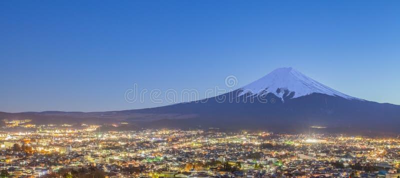 Fujiyoshida stad på nattetid med Mount Fuji arkivbilder