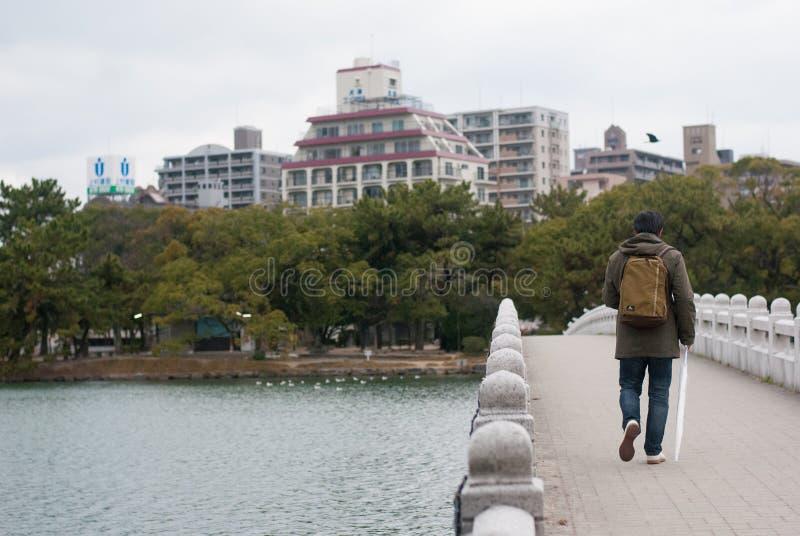 Fukuoka, Japão - 1º de janeiro de 2019: Uma trouxa levando do homem e guardar o guarda-chuva branco que anda na ponte de pedra no imagens de stock
