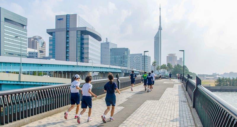 Fukuoka, Japão - 30 de junho de 2014: Os estudantes japoneses da High School que correm em Momochi encalham a estrada Esta estrad imagens de stock