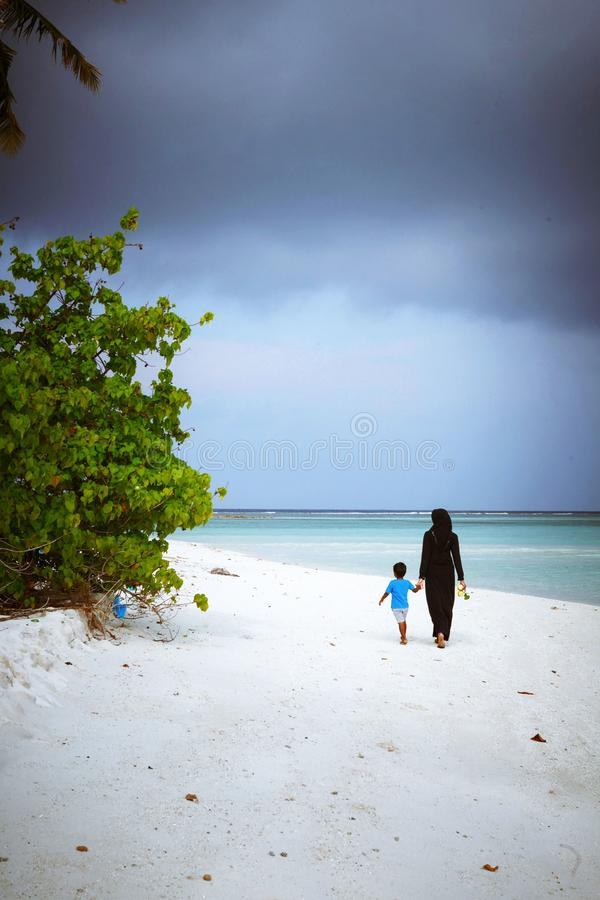 Muslim woman and child are walking in the beach of island small village. Fuldhoo, Maldives - December 10, 2016: Muslim woman and child are walking in the beach royalty free stock images